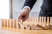 Wooden Game Strategy, Businessman Hand Stopping Falling Wooden Dominoes Effect From Continuous Toppl poster