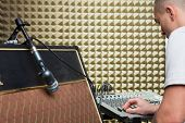 Guitar player in recording studio at sofa with guitar amplifier and audio systems