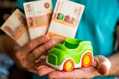 Hand Hold Green Toy Car And Russian Money.fixed Rate For Car Loan, Or Saving Money For Car, Trade Ca poster