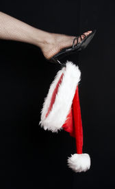 pic of santa claus hat  - Santa cap hanging from high heel of an elegant shoe - JPG