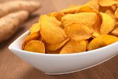 foto of nibbling  - Crispy Peruvian sweet potato chips in white ceramic bowl with sweet potatoes in the back (Selective Focus Focus one third into the sweet potato chips)