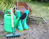 Instruments For Work In A Garden Is A Watering-can, Rubber Knee-boots And Wheelbarrow