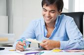 Happy young male interior designer looking at color swatches