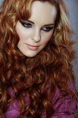 beautiful woman with long curly red hair and dramatic smoky eyeshadow on studio background