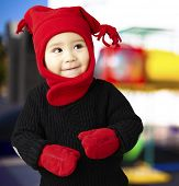 portrait of an adorable kid smiling and wearing winter clothes against an abstract background