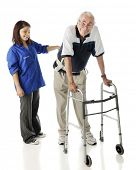 A young teen volunteer keeping an elderly man secure as he ambulates with his walker.  On a white ba