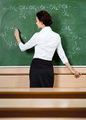 Teacher writes chemical formula at the blackboard