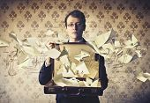 pic of gravity  - Young businessman holding an open briefcase with paper sheets flying away from it - JPG