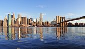 Brooklyn Bridge mit niedrigeren Manhattan Skyline Panorama am Morgen mit Wolke und Fluss-Reflexion