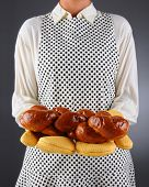 Closeup of a homemaker in an apron and oven mitts holding a freshly baked loaf of challah bread. Horizontal format over a light to dark background. Woman is unrecognizable. Shallow depth of field.
