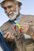 Happy senior man tying a fly fishing lure