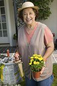 Portrait of happy senior woman holding pruner and flower pot in garden