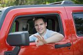 Young Driver Smiling Sitting in Driver Seat with Red SUV
