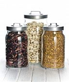 various legumes in the jars on white table