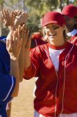 Female softball players giving high five after a winning game