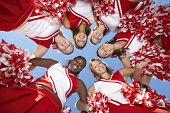 Low angle view of happy cheerleaders forming a huddle against clear sky