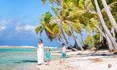 Panoramic photo of beautiful mother and two kids on a deserted island
