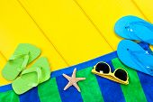 A beach towel, flip flops and sunglasses on a colorful yellow wooden deck with the presence of a sta