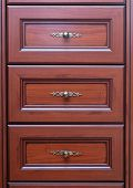 stock photo of armoire  - Classical brown wooden chest of drawers with decorative handles - JPG