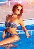 Mulher bonita à beira da piscina, sedutora modelo bronzeada posando na água-piscina, moda maiô,
