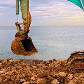 Excavating Rocks By The Sea