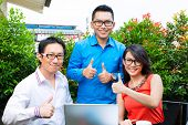 Asian Creative team working outdoor on laptop and have a brainstorming