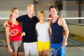 Group of men and women look forward to badminton in a fitness club