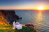 stock photo of rest-in-peace  - Couple in hug watching sunset on the edge of the cliff - JPG