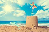 Sandcastle on sandy beach with pinwheel against a summer sky - vintage feel