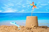 Sandcastle with windmill on summer beach