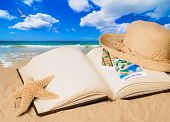 Summer book lying on sandy beach with straw sunhat