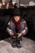 stock photo of beggar  - Poor beggar child sitting in a dark corner - JPG