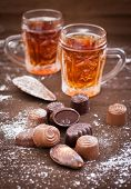 Chocolate Candy And Glass Cups With Tea On A Brown Background