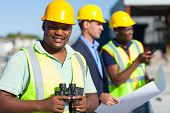 african construction worker holding binoculars standing with colleagues