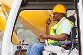 african industrial worker operating bulldozer while talking on walkie-talkie