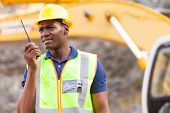 african american mine worker with walkie-talkie at mining site
