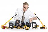Build up a brand concept: Smiling businessman building the word brand along with construction machin