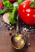 Spoon with Olive Oil and vegetables on wooden table