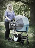 Picture of young mother with baby stroller  walking in the park.