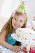 Young Girl Wearing Party Hat With Birthday Cake Smiling