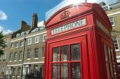 red phone booth in old style and typical brick building in London