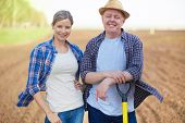 Image of two happy farmers on background of plowed field