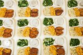 White styrofoam lunch boxes containing tofu, swiss chard, and rice