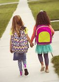 stock photo of little school girl  - Little girls walking to school together - JPG