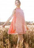 Pretty woman on a meadow wearing a beautiful orange dress