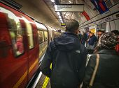 Passengers in London Tube station as train arrives