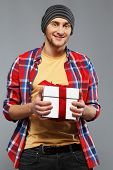 image of beanie hat  - Stylish young man in shirt and beanie hat with gift box - JPG