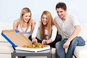stock photo of lunch box  - Group of young people eating pizza at home - JPG