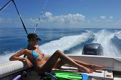 Girl relaxing on the back of motor boat
