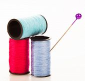 Three reels of colourful cotton yarn with a plastic topped sharp pin for sewing, embroidery and tail